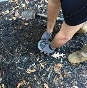 pest control technician installing termite bait station